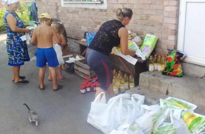 Rozdělování přivezené humanitární pomoci ve vesničce na frontě (a kotě). Foto: Tadeáš