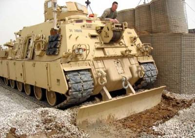 Jak dělat jednoduché práce zábavnou formou. Vyprošťovač tanků hloubí příkop pro elektrický kabel na kontrolním stanovišti 3, severní Irák. | Easy jobs through entertaining means. A tank rescue vehicle is digging a trench for an electric cable at check-point 3, northern Iraq.